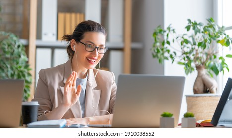 Happy casual beautiful woman working on a laptop, talking with somebody in office.