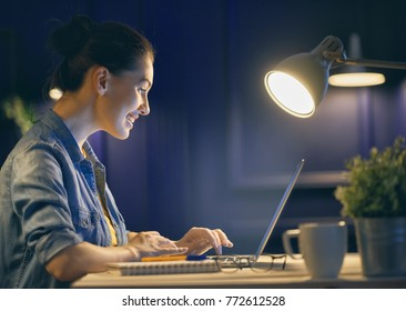 Happy casual beautiful woman working on a laptop at the night at home.