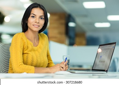Happy casual businesswoman sitting at the table in office and looking at camera