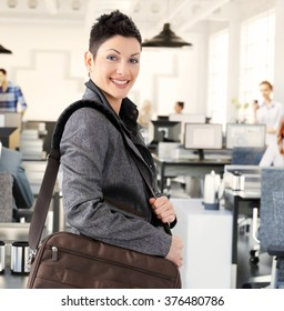 Happy casual caucasian businesswoman arriving to office with shoulder bag. Standing, looking at camera, smiling.
