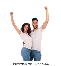 happy casual couple celebrating success with hands in the air on white background