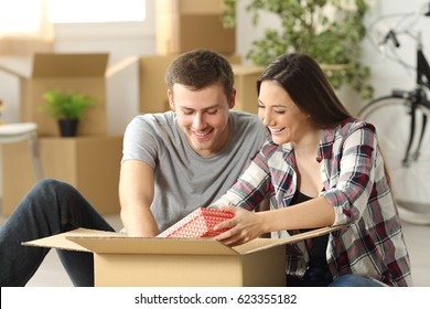 Happy casual couple sitting on the floor unpacking a box while moving house  in the living room
