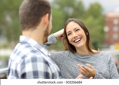 Happy casual couple talking looking each other sitting in a balcony with a green urban background
