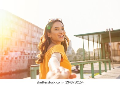 Happy casual girl holding hand and looking behind while walking in the city street. Beautiful latin woman walking around the city. Young smiling woman pulling her boyfriend and looking at camera.