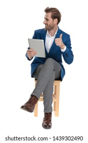 Happy casual guy giving a thumb up and holding his tablet while looking to the side and sitting with his legs crossed on white studio background