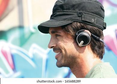 happy casual guy listening to player in earphones