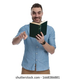 Happy casual holding book and pointing, laughing while wearing blue shirt, standing on white studio background