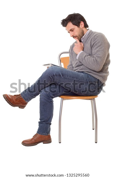 happy casual man on a chair with a tablet pc, isolated on white background