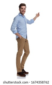 Happy casual man presenting and smiling with hand in pocket while wearing shirt and standing on white studio background