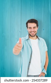 Happy casual man showing thumbs up against wooden planks background