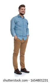 Happy casual man smiling with his hands in his pockets while standing on white studio background