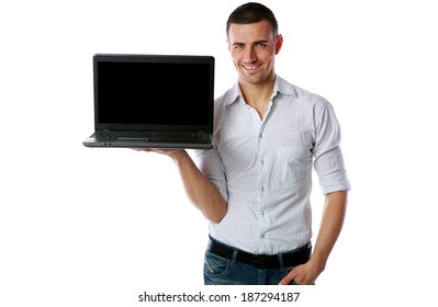 Happy casual man standing and showing laptop with blank screen over white background
