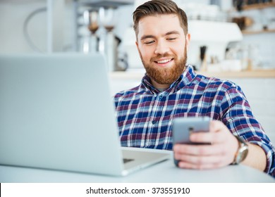 Happy casual man using smartphone and laptop computer in cafe