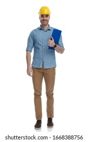 Happy casual man wearing construction helmet and holding clipboard, standing on white studio background