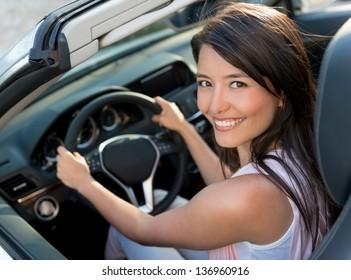 Happy casual woman driving a convertible car