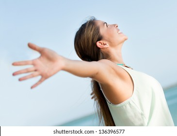 Happy casual woman with open arms outdoors