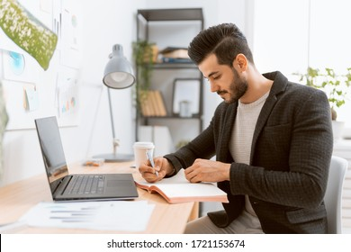 Happy casual young man working on a laptop at home.