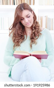 Happy casual young woman or student reading storybook on couch at home