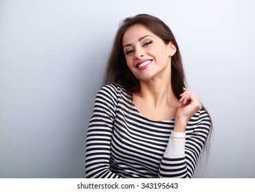 Happy casual young woman with wild toothy smiling looking on blue background
