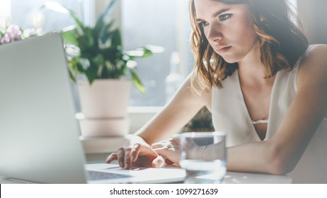 Happy caucasian beautiful woman working on a laptop sitting at the table in living room of modern house.Closeup.