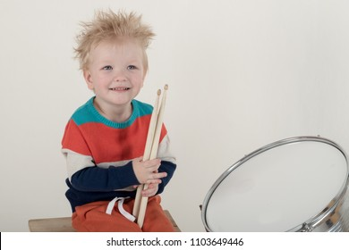 Happy Caucasian  blonde with drumstick. Drummer play on a new drum kit. Parents bought a drum box for training. Child in bright clothes with new chopsticks in hands happy at home. Bright emotions