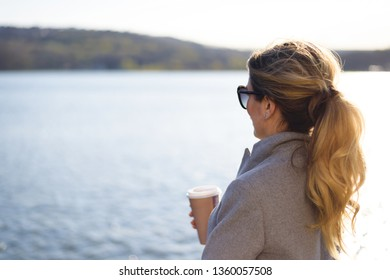 Happy caucasian blonde girl wearing black sunglasses drinking and holding cup of coffee by the blue lake