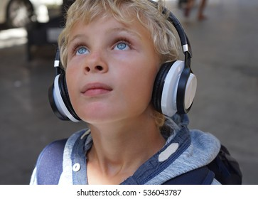 Happy Caucasian boy enjoying the music and looking up on the street. Handsome blond child with headphones.
