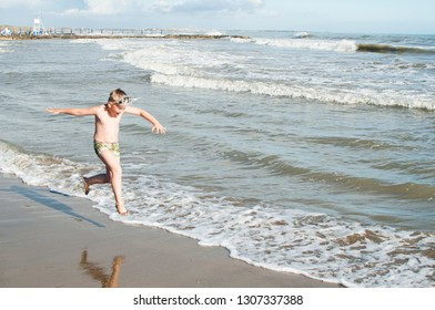 Happy caucasian boy running on italian beach