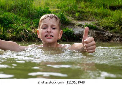 Happy caucasian boy swimming in the pond