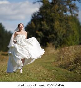 Happy caucasian bride walking field, wearing gorgeous dress.
