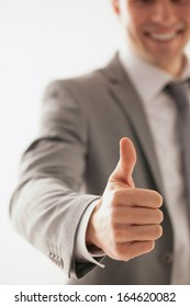 Happy Caucasian businessman showing thumbs up.