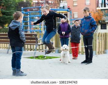 Happy caucasian children playing rubber band jumping game and laughing outdoors