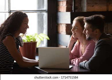 Happy Caucasian couple meeting with wedding planner or consultant in coffeeshop discuss ideas together, smiling man and woman talk consider project with female real estate agent in cafe