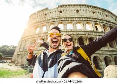 Felice coppia caucasica sta scattando un selfie sorridendo alla macchina fotografica davanti al colosseo di Roma