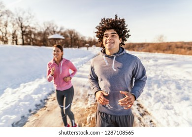 Happy caucasian couple wearing sportswear and running on the trail in nature. Winter fitness concept.