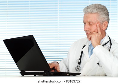 Happy Caucasian doctor with a computer sitting on a light background
