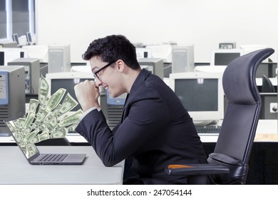 Happy caucasian entrepreneur looking money dollars on laptop computer at office