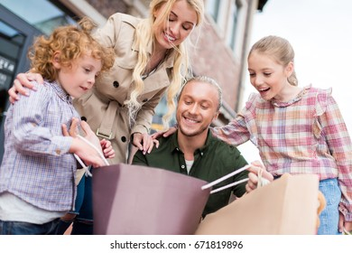 happy caucasian family looking into shopping bag on the street