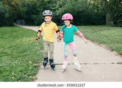 Happy Caucasian friends boy and girl in helmets riding on roller skates in park on summer day. Support and help from friend. Seasonal outdoor children activity sport. Kids individual summer sport.
