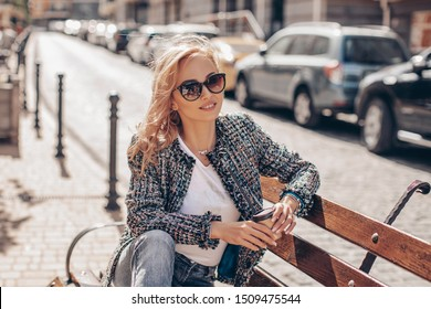 Happy Caucasian Girl enjoys the city streets of Paris. girl drinks coffee sitting on a bench in the park. Relaxed