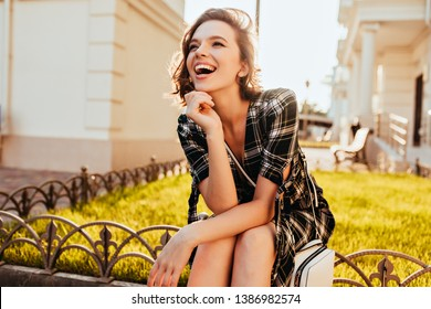 Happy caucasian girl looking in distance while posing in park. Refined short-haired woman in checkered attire enjoying sunny autumn morning.