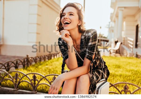公園でポーズをとりながら遠くを見る白人の幸せな女の子。晴れた秋の朝を楽しむチェックの衣装を着た上品な短毛の女性。