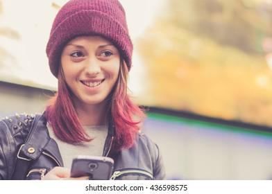 Happy caucasian girl smiling outdoor. Pretty tourist girl is using smartphone in a urban scene.