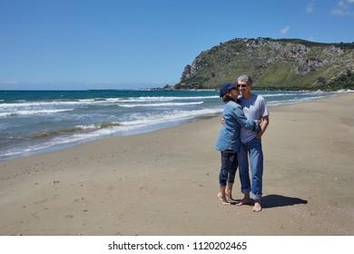 Happy Caucasian heterosexual couple barefoot on the beach.