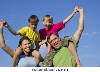 Happy Caucasian joy mother and father together with his sons play the fool on the street