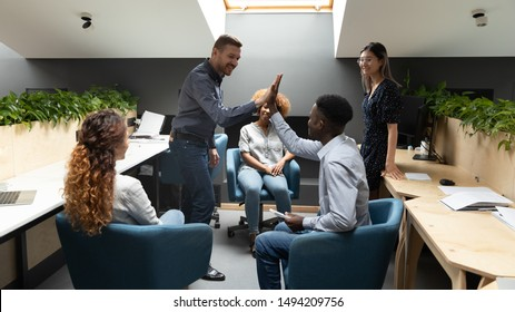 Happy caucasian male leader give high five motivate african employee at diverse group office meeting express friendship business agreement good teamwork result share company success at team briefing.