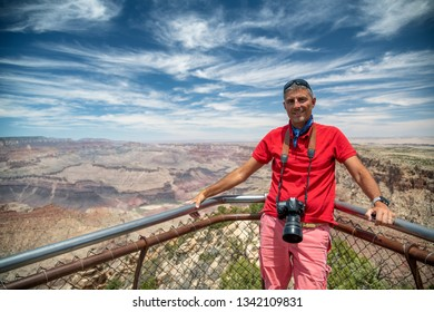 Happy caucasian male tourist visiting Grand Canyon.