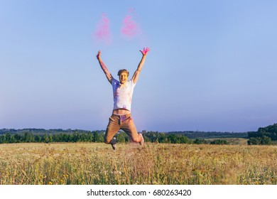 happy caucasian man jumping in field during holi festival