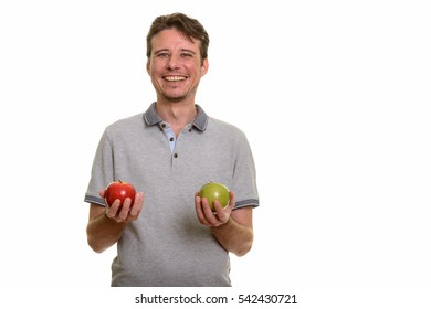 Happy Caucasian man smiling and holding red and green apple isolated against white background
