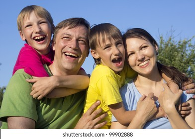Happy Caucasian mom and father together with his sons play the fool on the street